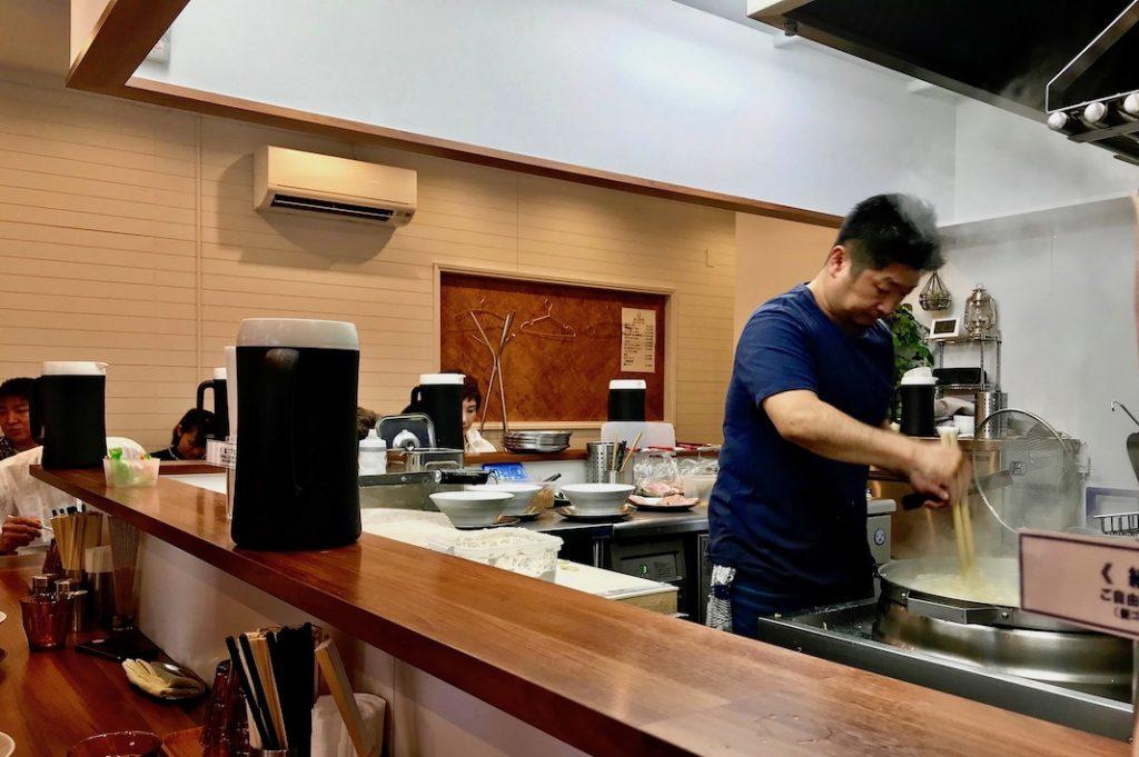 Watching him make ramen at the counter in Daruma
