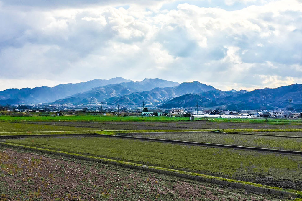 Open fields surrounded by mountain ranges characterize much of the Honshu landscape.