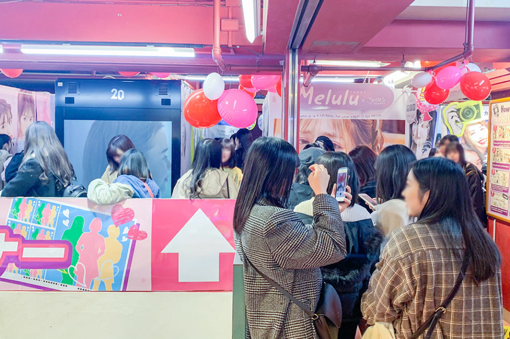 Teens wait for their turn at the Purikura photo booths in Shibuya