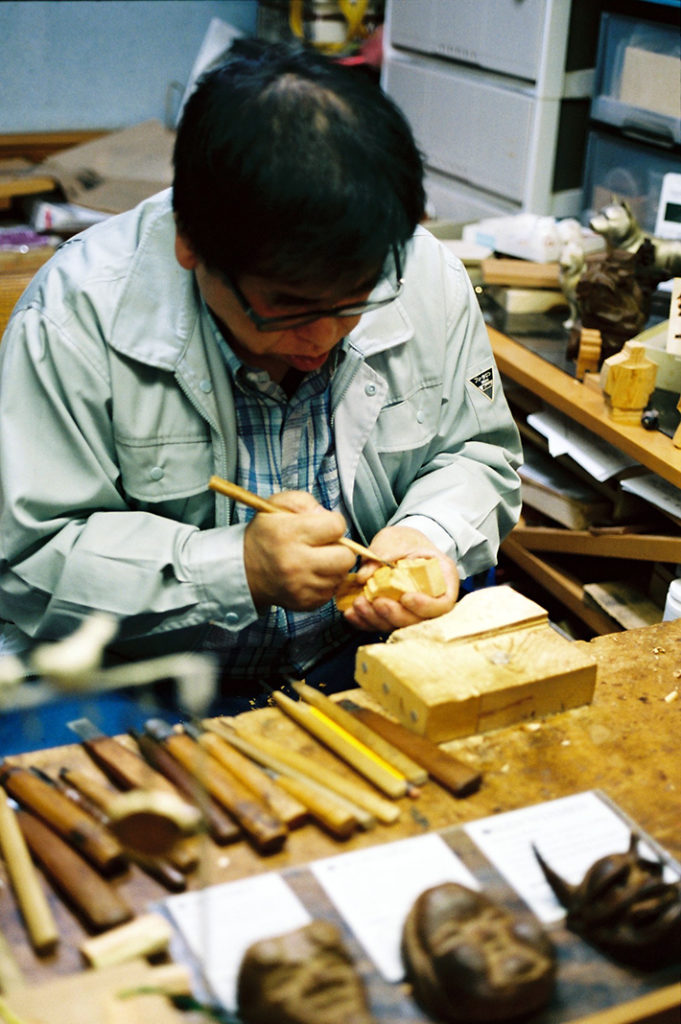Employed craftsmen sit in deep concentration as they whittle and carve traditional Japanese artifacts.