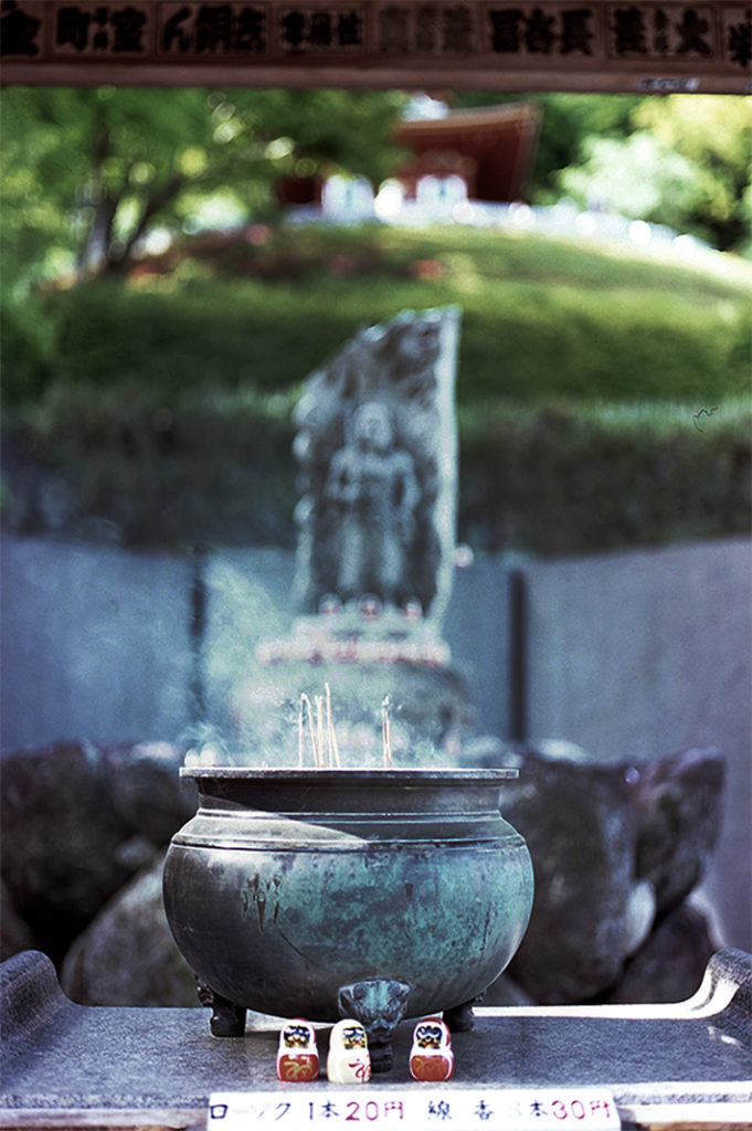 An incense bowl burns before a carved statue of Fudō-myoō at the lower levels of the temple.