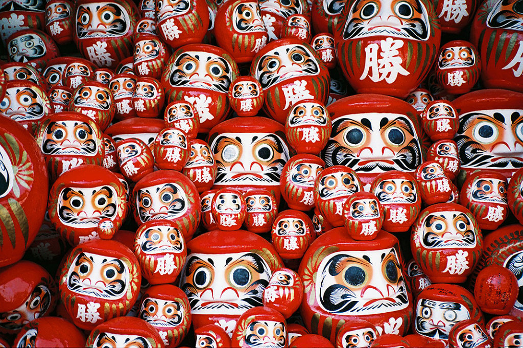 Darumadness! Hundreds of bright red Daruma dolls are stacked high at the lower levels of the temple.