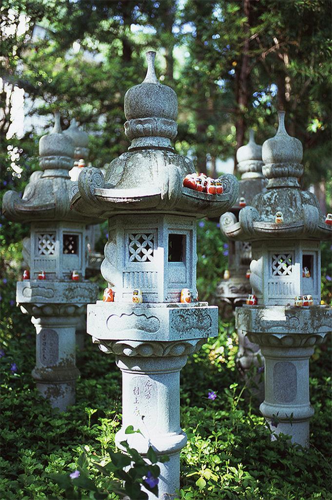 Tiny wooden Daruma sit dotted across three stone lanterns, backed in the green woodland of Katsuō-ji.