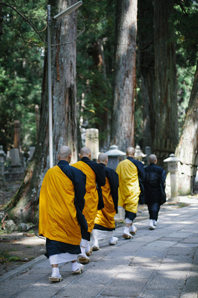 A line of Buddhist monks walk the stone path of Okuno-in in Kōya-san.