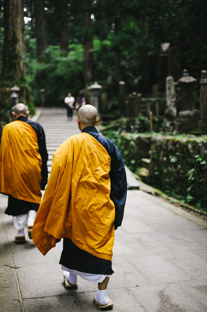 Buddhist monks walk away from the mausoleum as two Japanese pilgrims stop to observe, deep in the cedar forests of Kōya-san.