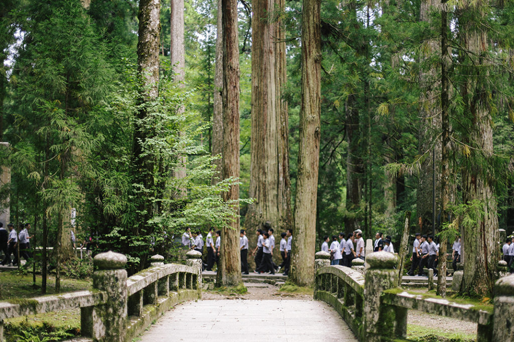 A sea of white-shirted schoolchildren walk in a line along a pathway shrouded in trees, set behind a stone bridge deep in Kōya-san's Okuno-in.