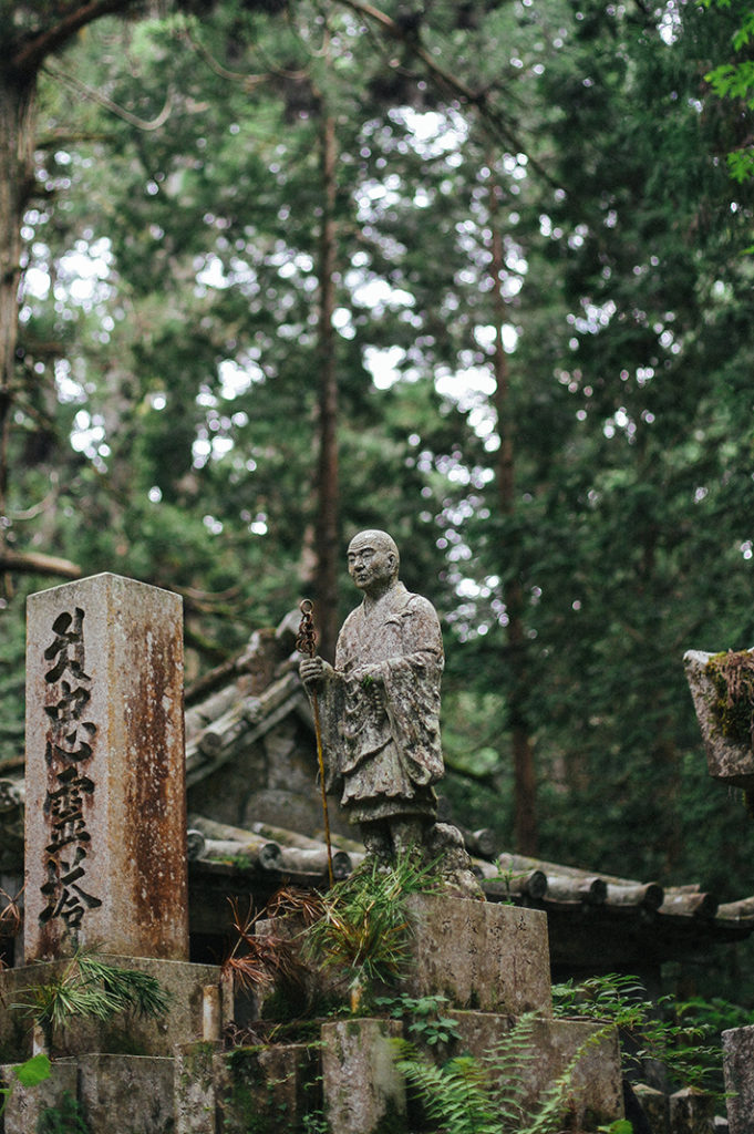 A stone statue of the Buddhist master Kukai stands surrounded by cedar trees and ferns in Kōya-san.
