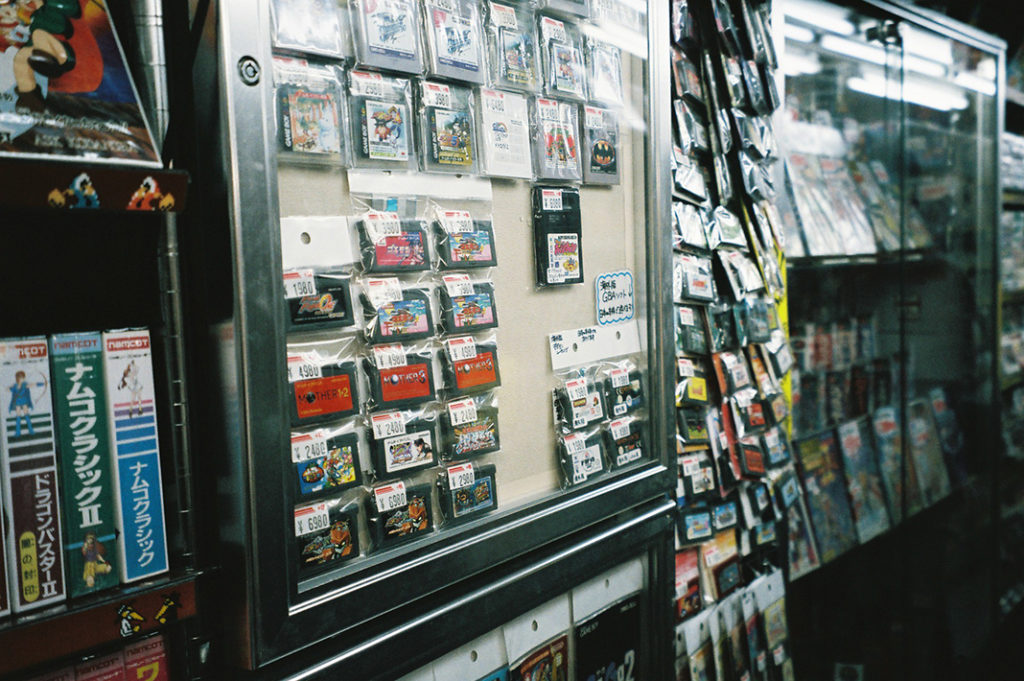 Game cartridges from the 1990s line the walls in many of the district's used gaming goods stores.