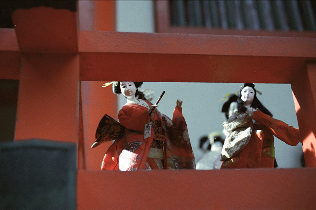 Figurines watch silently from the vibrant red balconies.