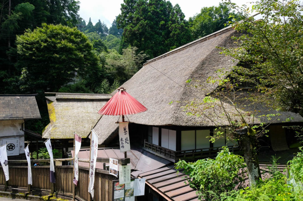 The iconic thatched roof of Higashibaba Guest House, a Mitakesan accommodation.