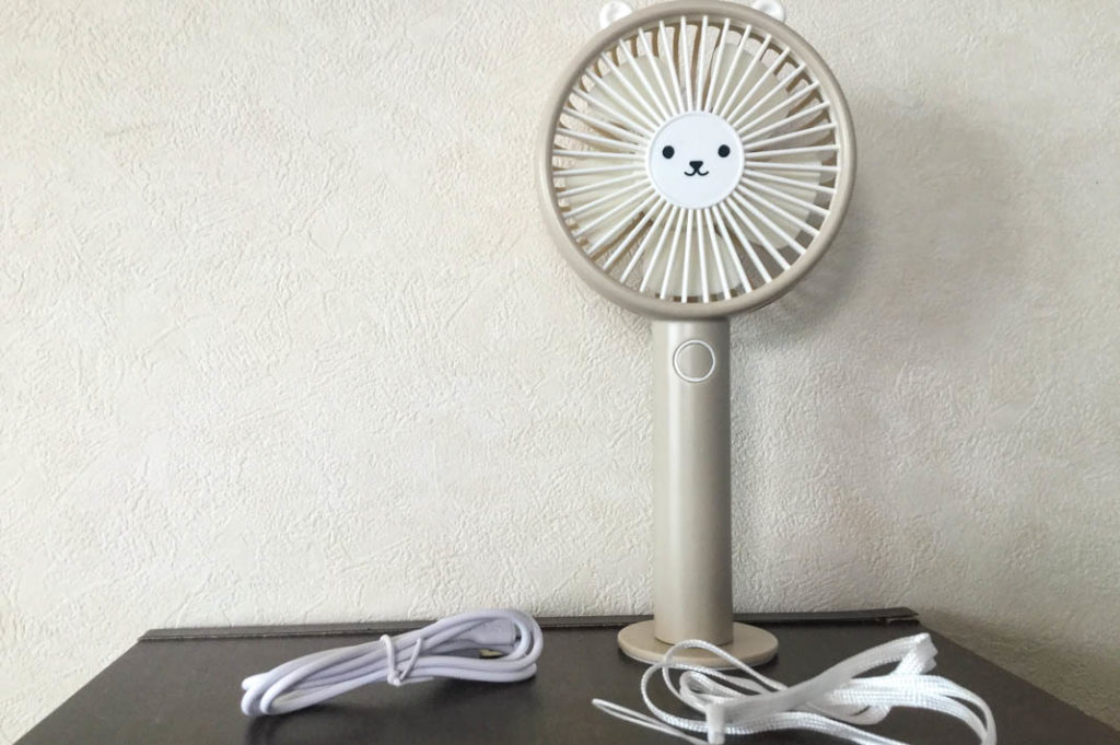 USB fan shown with stand, charger, and hanging strap.